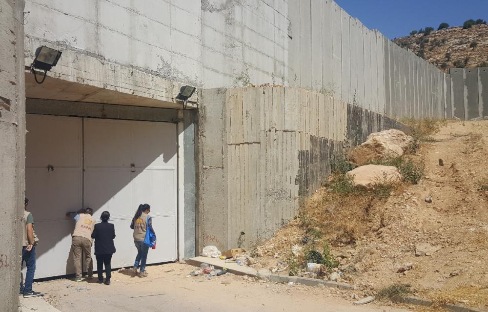 Genom en glipa i porten går det att spana ut över Sohaiila och Naims mark. Den öppnas bara tre dagar om året, i och med olivskörden. Foto: S. Sjöblom