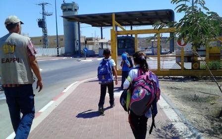 Tre barn och en följeslagare på väg mot en vägspärr i South Hebron Hills.