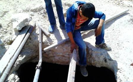 En pojke dinglar med benen i en förstörd vattencistern