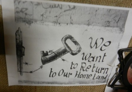 """Plansch med texten """"We want to return to our home land"""""""