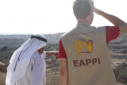 Ryggarna på en följeslagare och en palestinier som blickar ut över ett landskap.