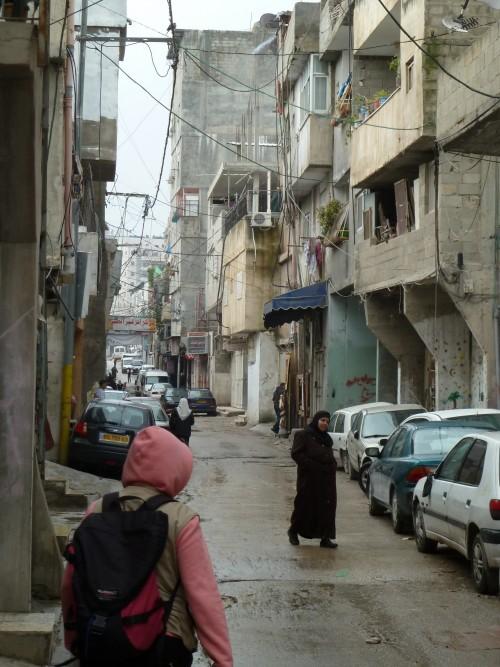 En följeslagare går på gatan i flyktinglägret Shufat.