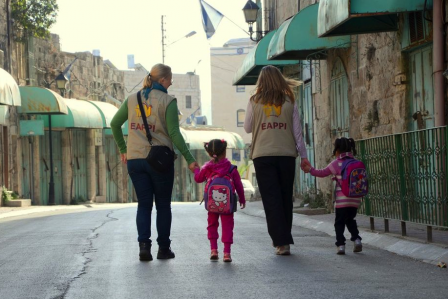 Två följeslagare följer två barn till skolan på Shuhada Street i Hebron.