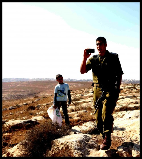 En israelisk soldat kommer gående och filmer med sin telefon. I bakgrunden en palestinsk pojke.