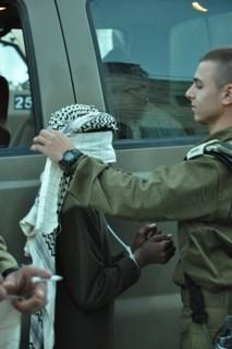 En soldat sätter ögonbindel på ett palestinskt barn vars händer är bundna.