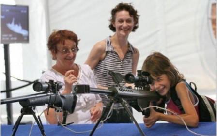 Dotter, mor och mormor tittar på vapen på vapenmässa i Israel.