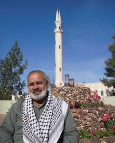 Haj Sami Sadiq, borgmästare i al-Aqaba framför byns moské.