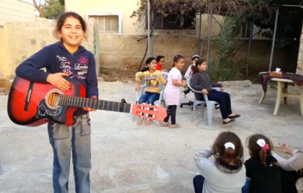 Shaima' spelar gitarr på följeslagarnas innergård i Jayyous.