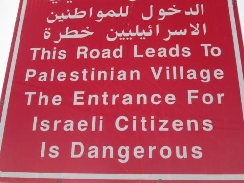 """Ungefär så här lyder texten översatt till svenska: """"Den här vägen leder till en palestinsk by. Det är farligt för israeler att åka in här""""."""