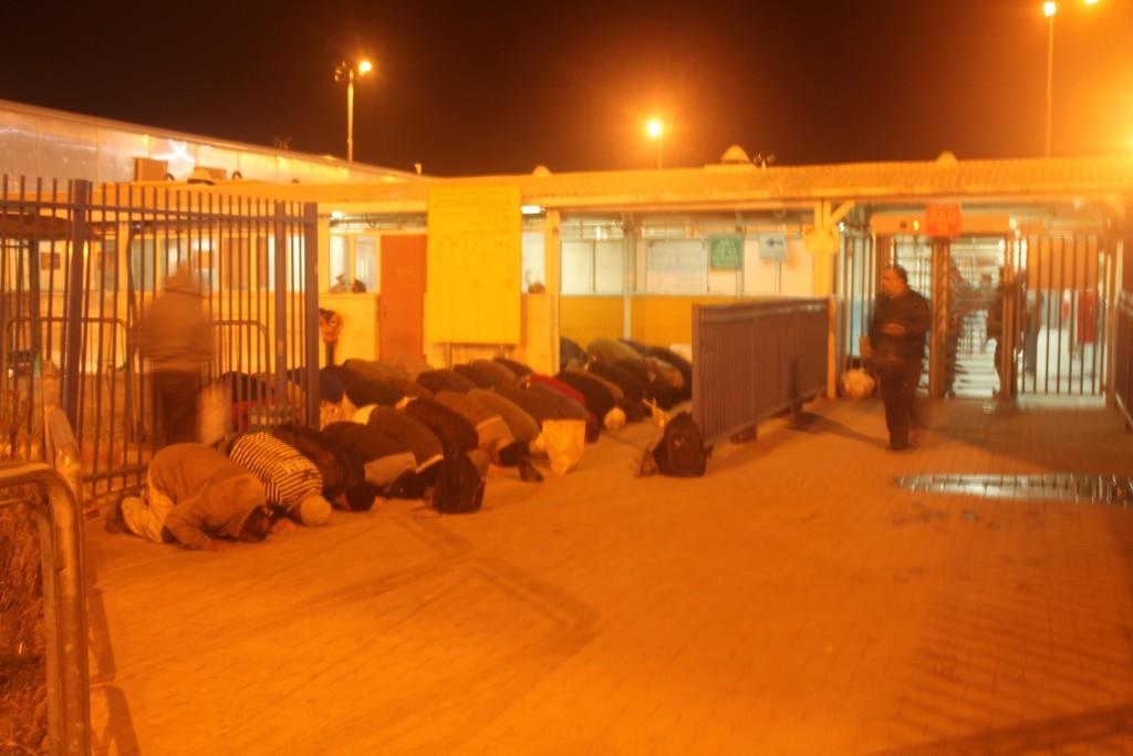 Klockan är 05.10, och det är dags för morgonbönen utanför vägspärren Qalandiya.