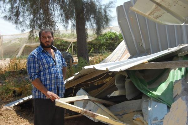 Tvåbarnspappan Yakoub, 24 år, framför det rivna huset. Bakom honom skymtar en vindruvsodling som tillhör en bosättning.