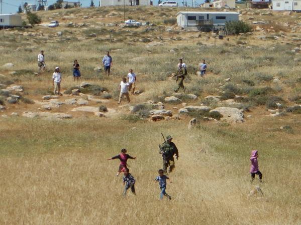 Palestinska barn, skyddad av israelisk militär, flyr undan israeliska bosättare.