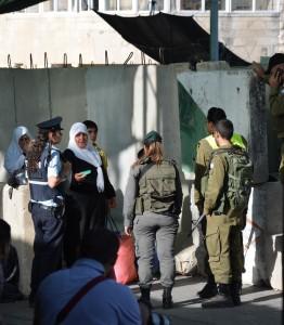 Soldater som kontrollerar ålder på en kvinnas son vid vägspärr 300.