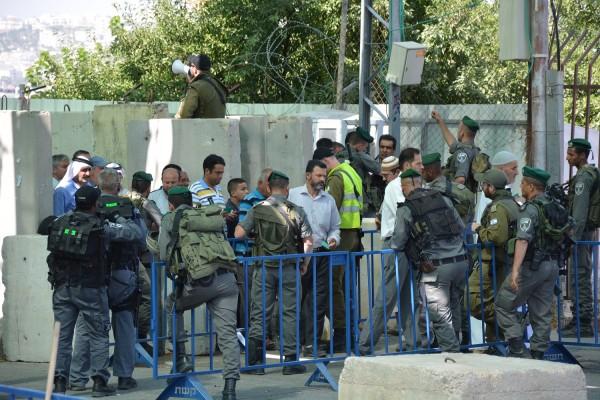 Män köandes vid vägspärr 300, i väntan på att få sin ålder och identitet kontrollerad av israeliska soldater.