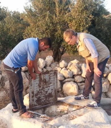 Nasser visar mig en av de nedgrävda vattencisterner som ligger precis utanför den israeliska utposten norr om Susiya.