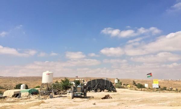 En av vattencisternerna mitt i Susiya och traktorn som används för att frakta vatten till byn.