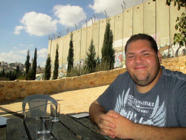 Tarek Al-Zoughbi sitter i Wi´ams trädgård alldeles intill muren och pratar om sitt lands framtid. Bild: Susanne
