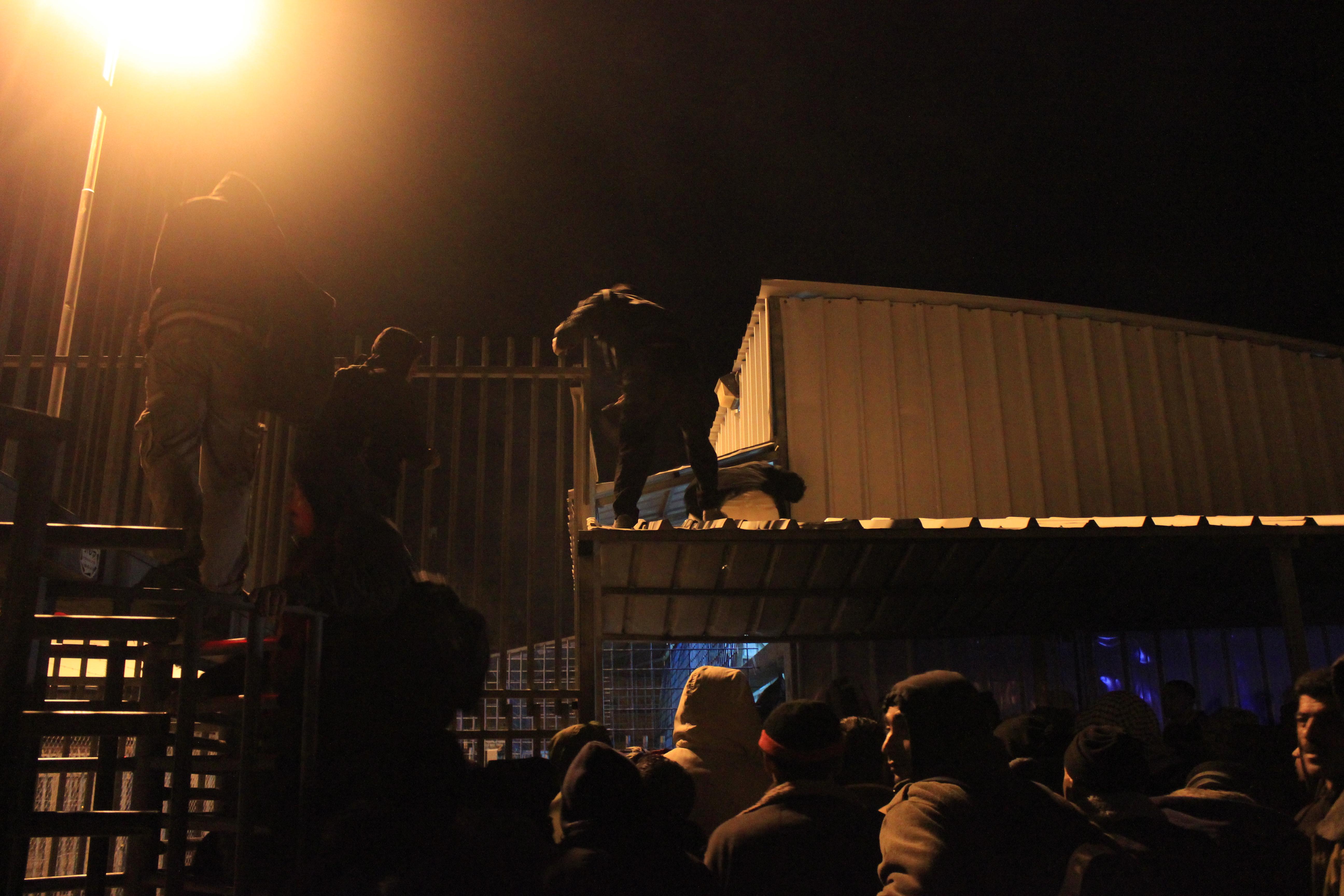 Män klättrar över staketet vid Tarqumiya kontrollstation.