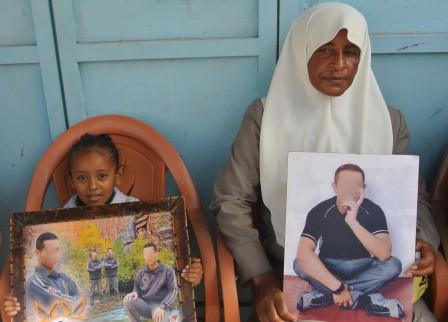 En palestinsk kvinna och ett barn sitter med bilder av fängslade släktingar.