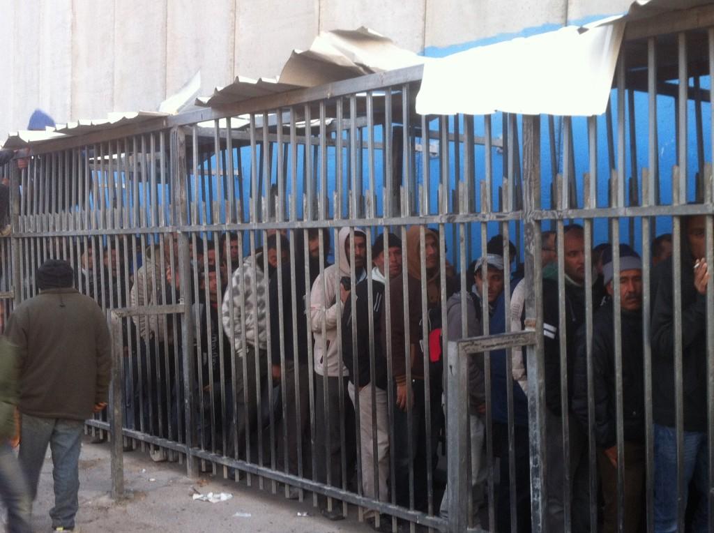 En kö av män bakom galler vid vägspärren Gilo.
