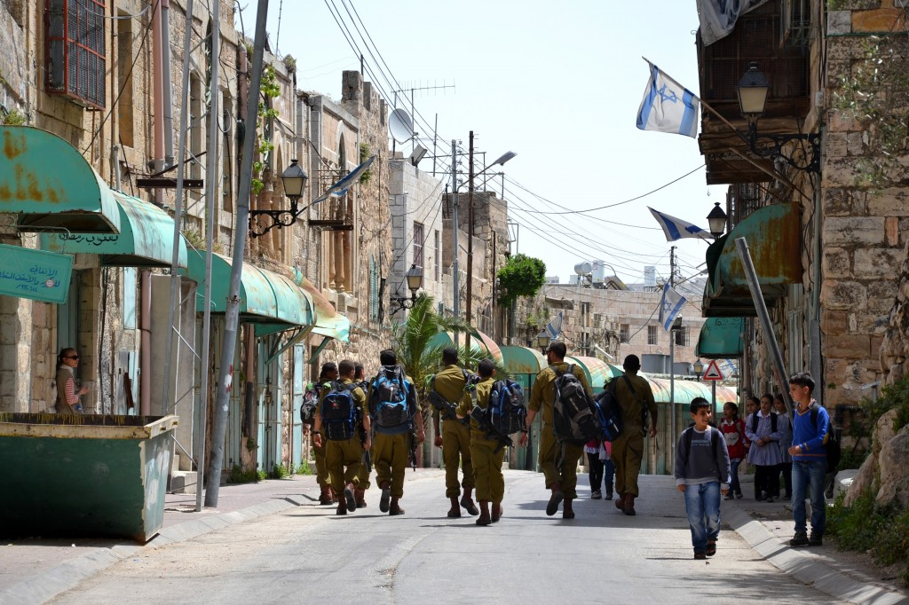Skolbarn möter israelisk militär på Shuhada Street i Hebron