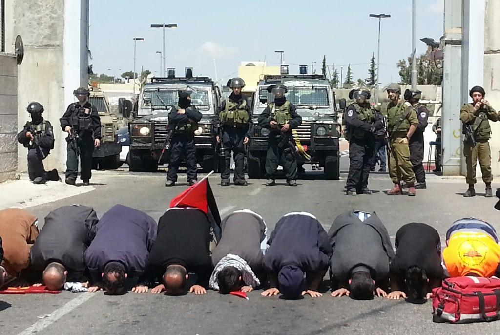 Muslimska män förrättar bön framför muren. Bakom dem står en rad med israelisk militärpolis och soldater.