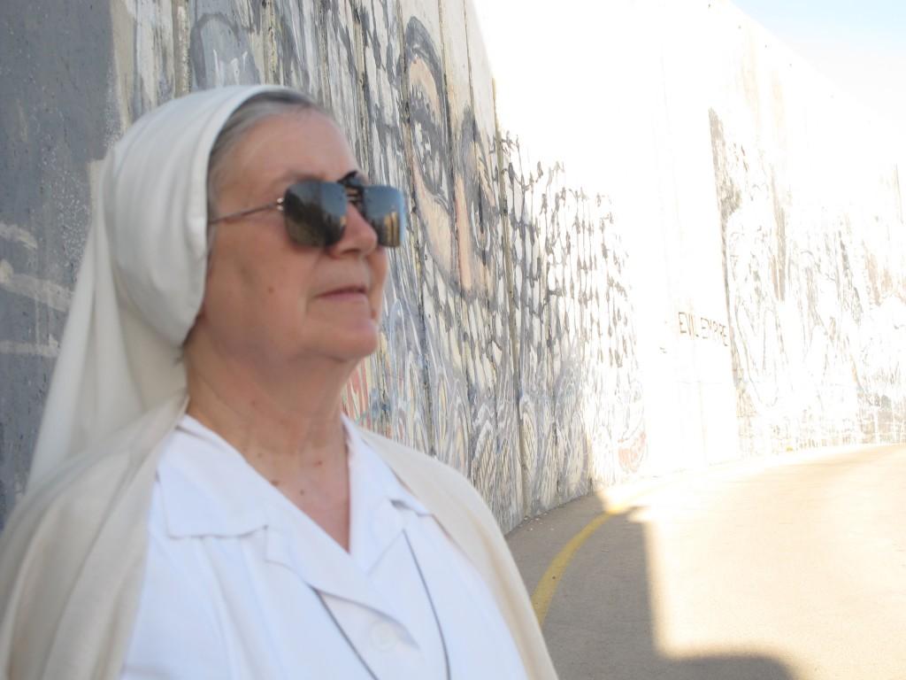 Syster Lucia Gemma i kvällssol intill muren.