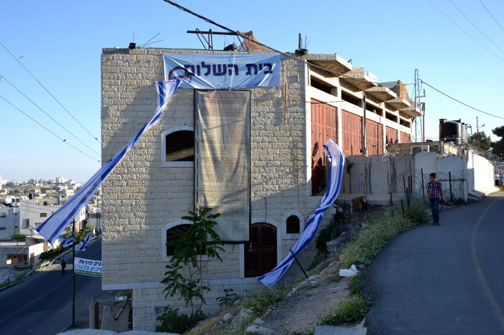 """Rajabi-huset. Bannern visar """"Beit HaShalom"""" - fredens hus och under denna sitter domslutet från Israels högsta domstol som slutligen ledde till att de israeliska bosättarna kunde flytta in."""
