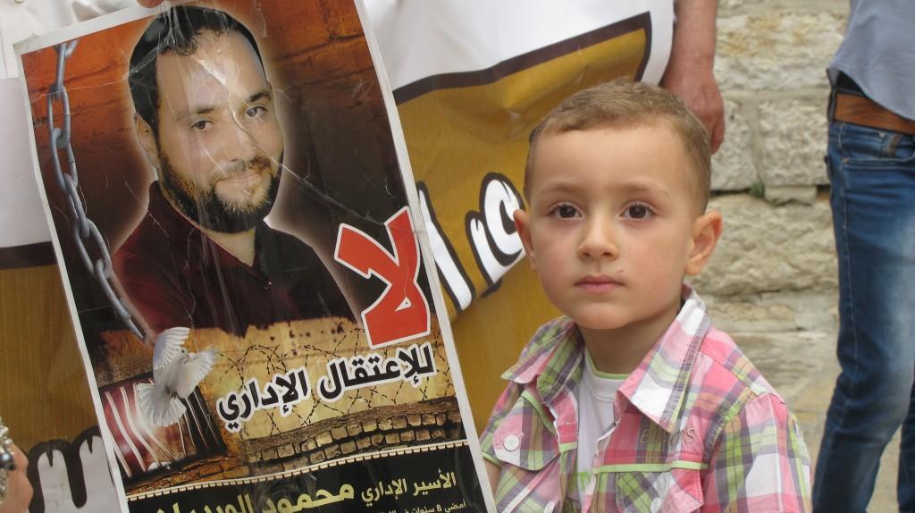 """Hassan håller stadigt i skylten med bilden av sin pappa Mahmoud al-Wadiyan. På skylten står det """"NEJ till administrativt förvar"""" på arabiska."""