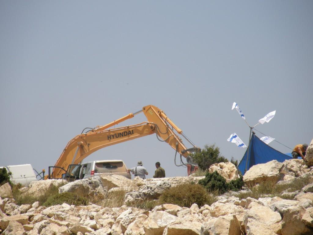 På bilden syns en arbetande grävmaskin och ett tält med israeliska flaggor