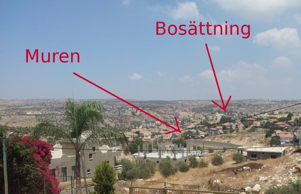Bild från Azzun Attma över byn med vy över muren och närmaste bosättning.