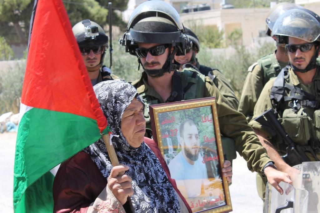 """Kvinna med porträtt av fängslade sonen Ziad under fredlig demonstration i al-Masara. Texten lyder """" Haifa, Jaffa, Bissam"""", """"Dömd till 27 år"""", """"Fånge, Ziad""""."""