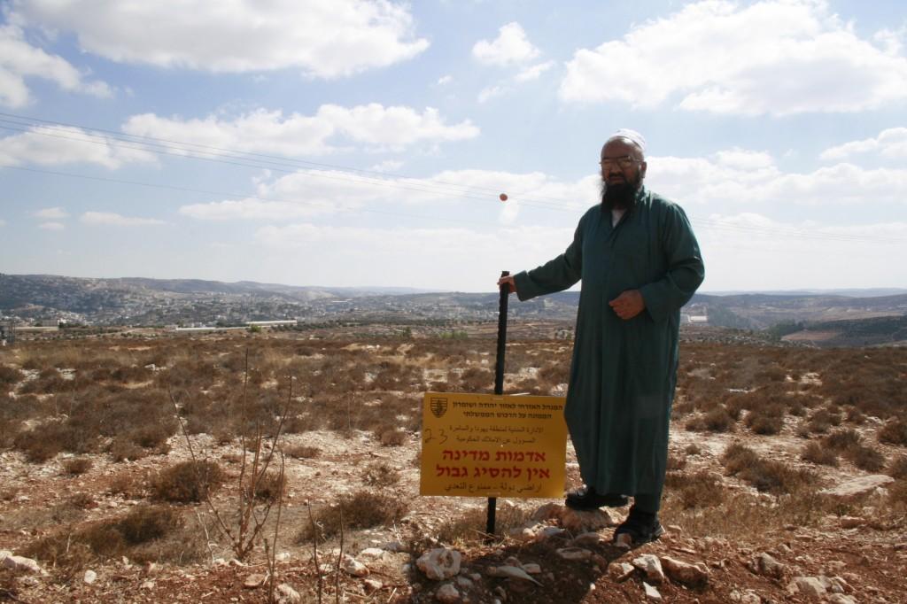Sheik Nasser star bredvid skylten som deklarerar hans mark statligt land.