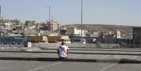 Marco sitter i sin peruanska landslagströja utanför vägspärren Qalandiya och tittar ut mot Ramallah.
