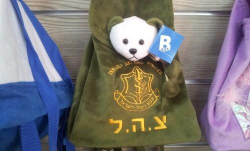 Ett exempel på ett militäriserat samhälle – en ryggsäck för skolbarn med en nallebjörn och israeliska arméns emblem.