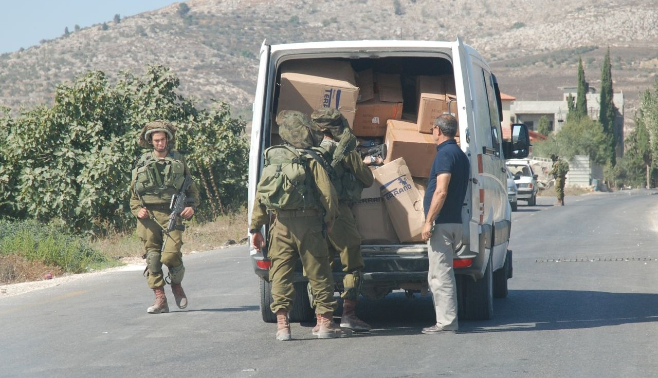 En tillfällig vägspärr utanför den palestinska byn Burin. Israelisk militär stoppar och kontrollerar oannonserat passerande palestinska fordon.