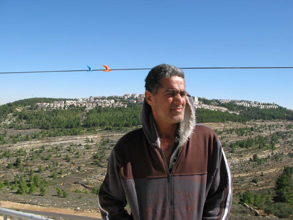 Omar Hajajlah på sin veranda. I bakgrunden ser man israeliska bosättningar.