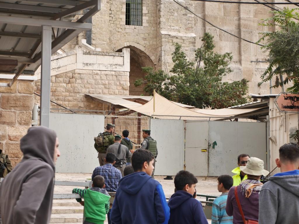 Ung palestinsk man förs bort av soldater vid ingången till Ibrahimimoskén.