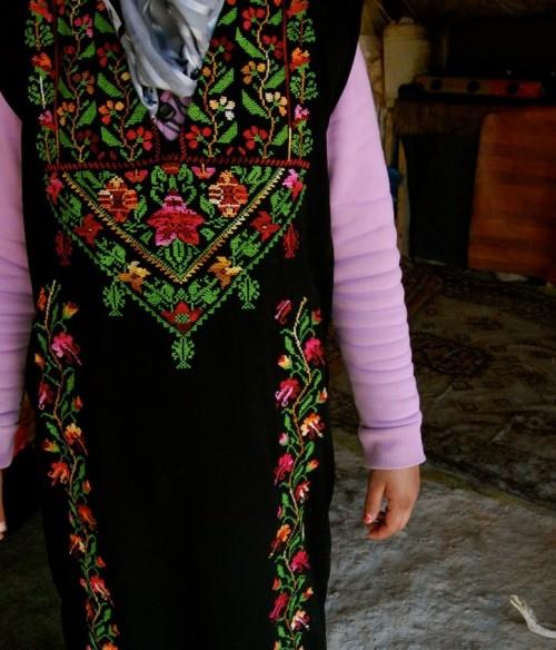 Raba visar stolt upp den traditionella klänningen med Tamams broderier.