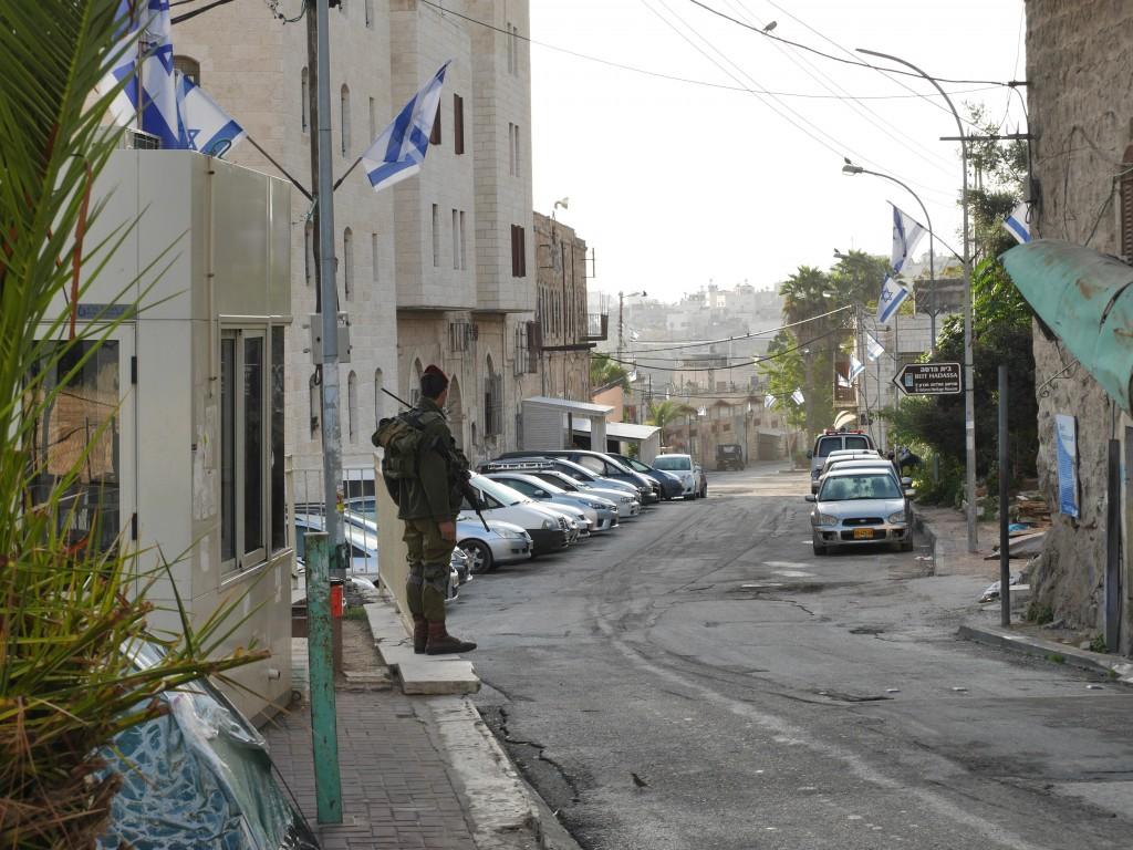 Soldat som vaktar vägspärr 55. Till vänster syns hans vaktkur. Rakt fram delen av Shuhadagatan som palestinier inte får gå på.