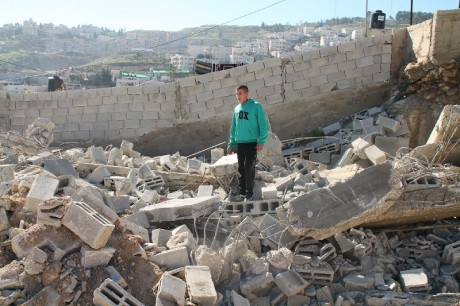 Aylan på resterna av sitt hus.