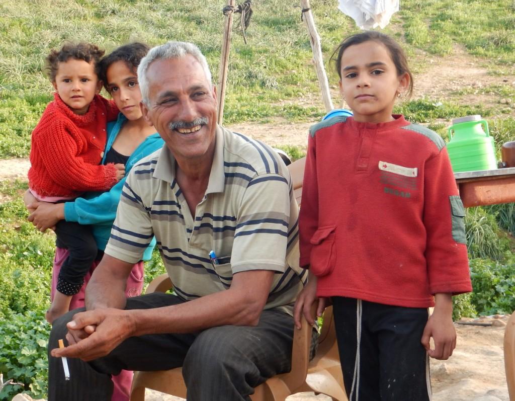 Nimer Daragmeh, omgiven av sina döttrar, kan skratta åt ett skämt trots att hans tältbostad skars sönder och revs för bara två månader sedan.