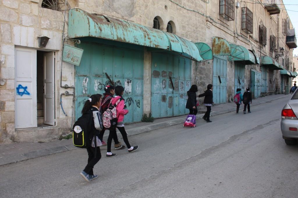 Barn på väg hem från skolan. Barnen går den sista sträckan på Shuhada Street. En gata som annars är avstängd för palestinier.
