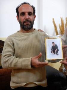 Baha's pappa visar upp bilden på sin son, 16 år gammal, som dömdes till nio månaders fängelse för stenkastning.