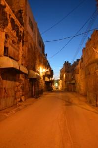 Shuhada Street på kvällskvisten. Förr Ii tiden sprudlade den av aktivitet, idag finns ett fåtal familjer kvar. Affärerna är stängda sedan länge.