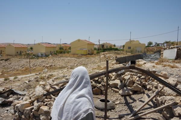 Ett rivet hus i Um al-Kher med en israelisk bosättning i bakgrunden.
