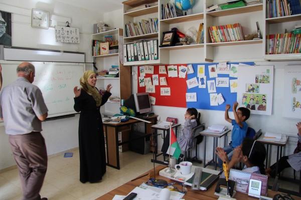 Läraren Alia Abu Yhadisel sjunger med de yngst skolbarnen. Foto: Sofia Magnusson