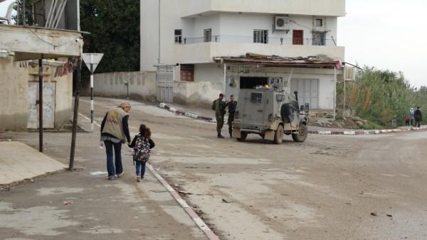 Följeslagare Sofia Claesson följer en liten flicka som är rädd för militären till skolan i al-Auja. Foto: Hannah Griffiths