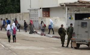 Barn på väg till skolan i al -Auja som passerar militärernas postering. Foto: Hannah Griffiths.