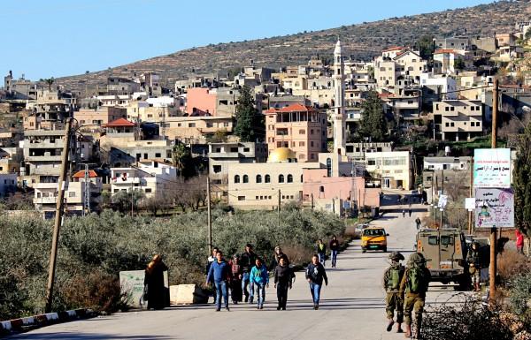 Barn närmar sig en vägspärr med soldater på väg till skolan, as-Sawiya, Västbanken. Foto: Alex Dunne